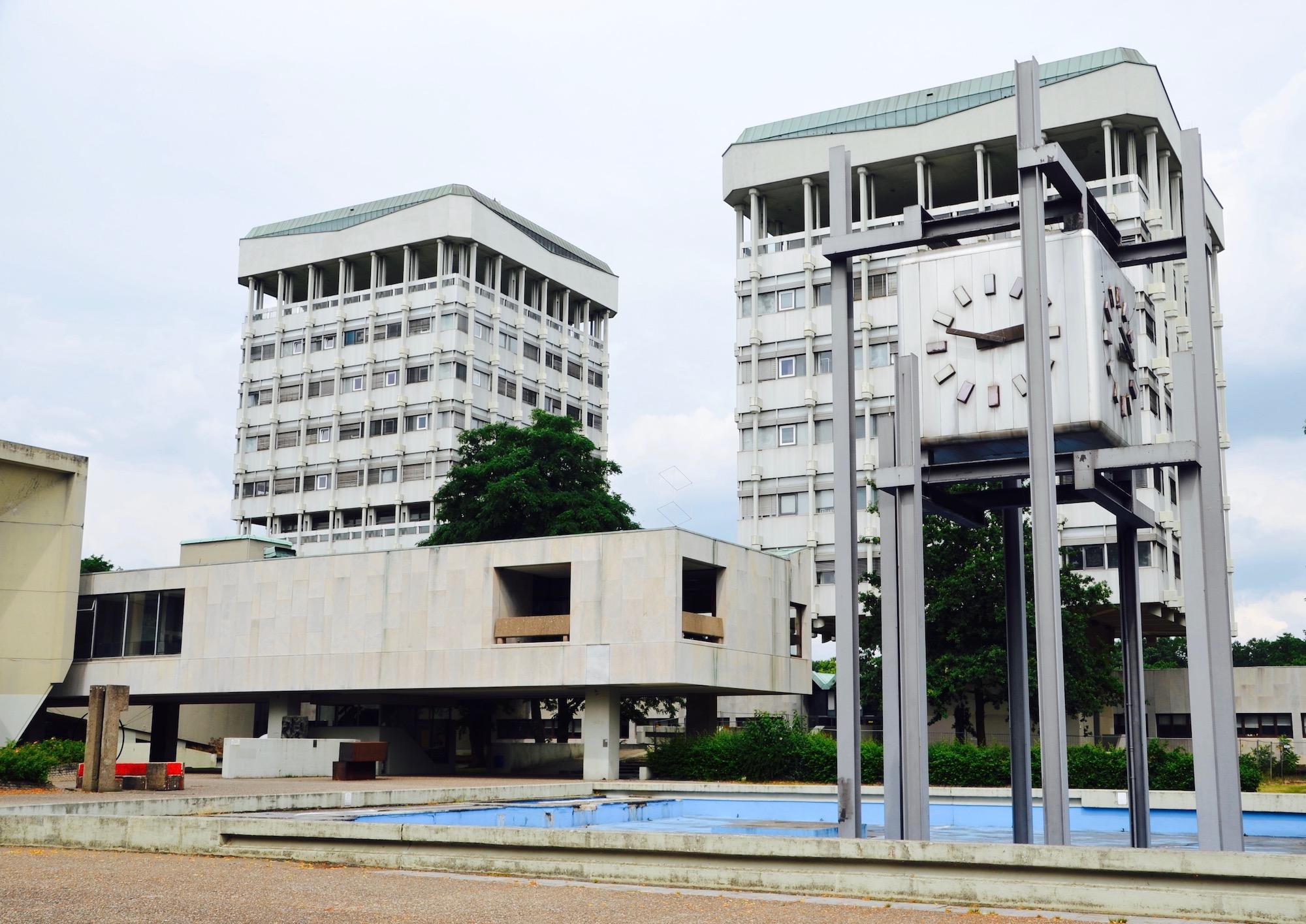 Zwei Verwaltungsgebäude, ein Brunnen und eine öffentliche Uhr