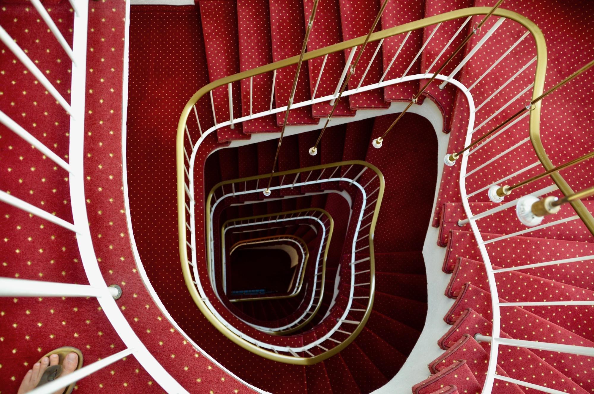 altmodisches Spiraltreppenhaus mit rotem Teppich