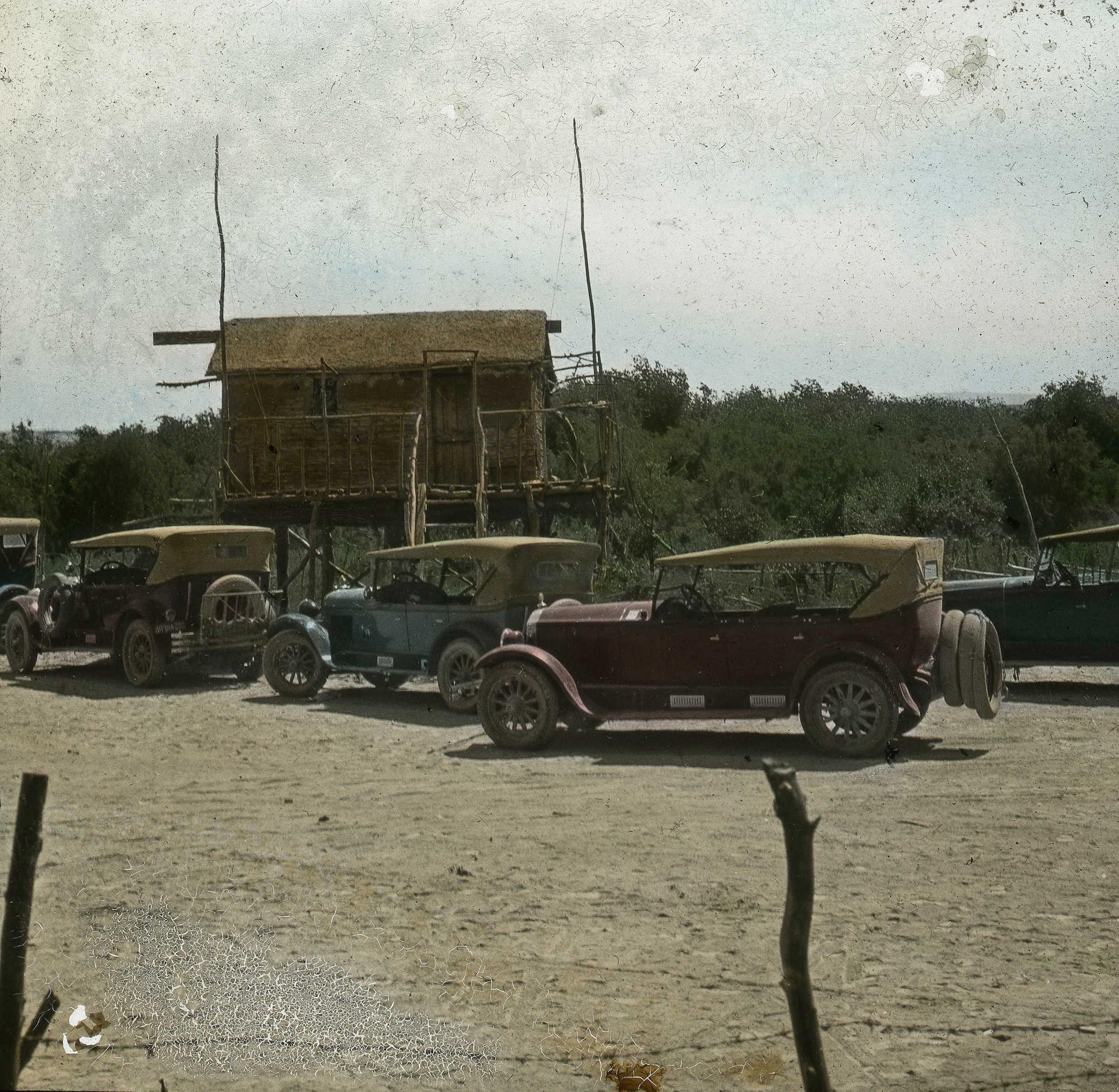 eine alte Farbfotografie: Man sieht mehrere altmodische Autos am Straßenrand geparkt