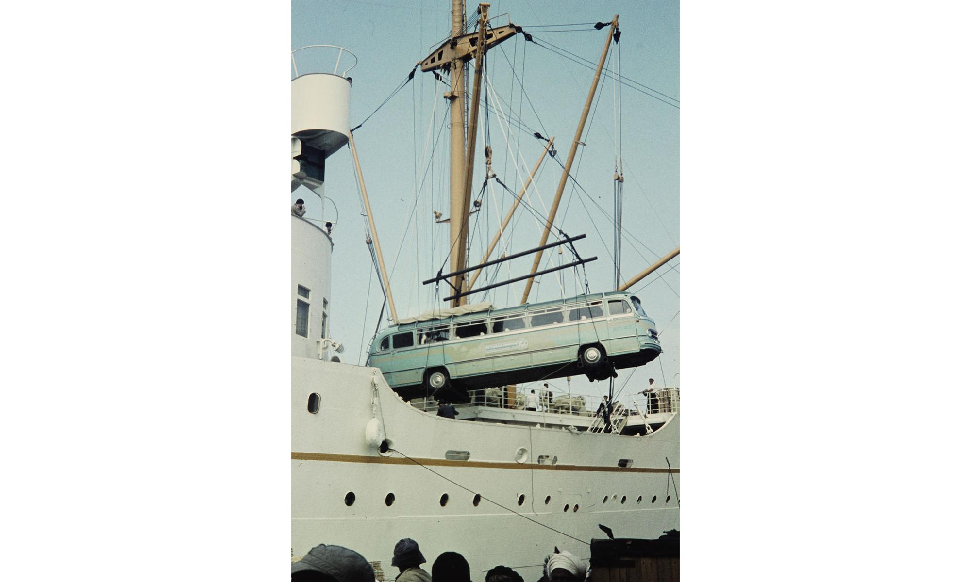 Ein altmodischer pastellfarbener Reisebus hängt an Seilen und wird gerade am Schiff verladen.