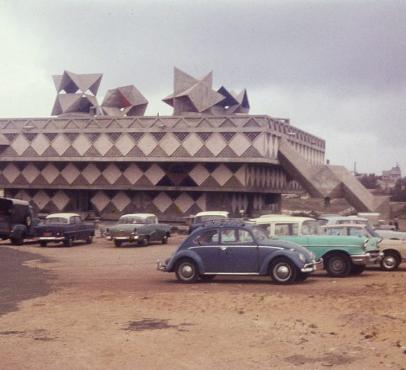 ungewöhnliche geformtest Betongebäude im Hintergrund, davor parkende Autos