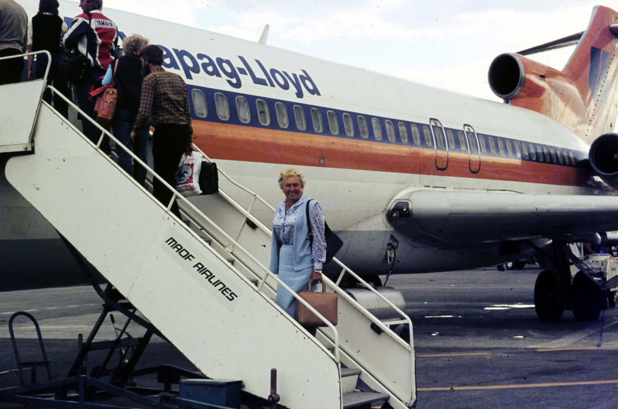 Frau auf Gangway zum Flugzeug dreht sich um und lächelt den Fotografen an. Flugzeug mit Hapag-Lloyd-Beschriftung.