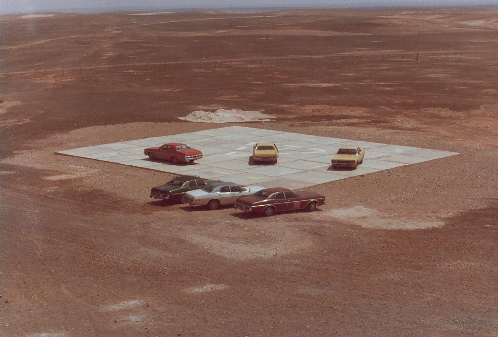Wüste, in der Bildmitte ein gepflasterter Hubschrauberlandeplatz. Darauf und daneben parken insgesamt sechs Autos