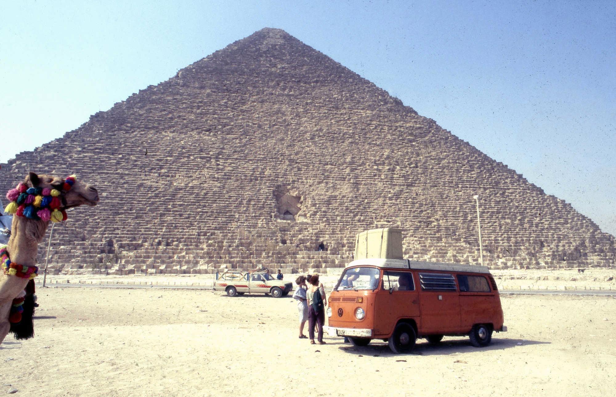 Pyramide in Ägypten, links guckt ein Kamel ins Bild, im Vordergrund ein orangefarbener VW-Bulli