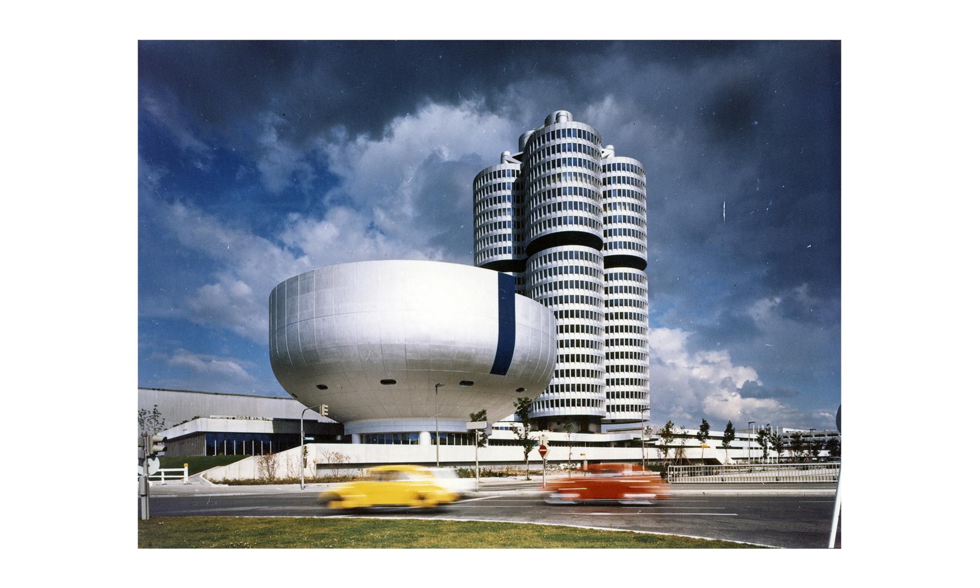 Zwei ungewöhnlich geformte silber glänzende Gebäude, davor schnell vorbeifahrende Autos in Rot und Gelb.