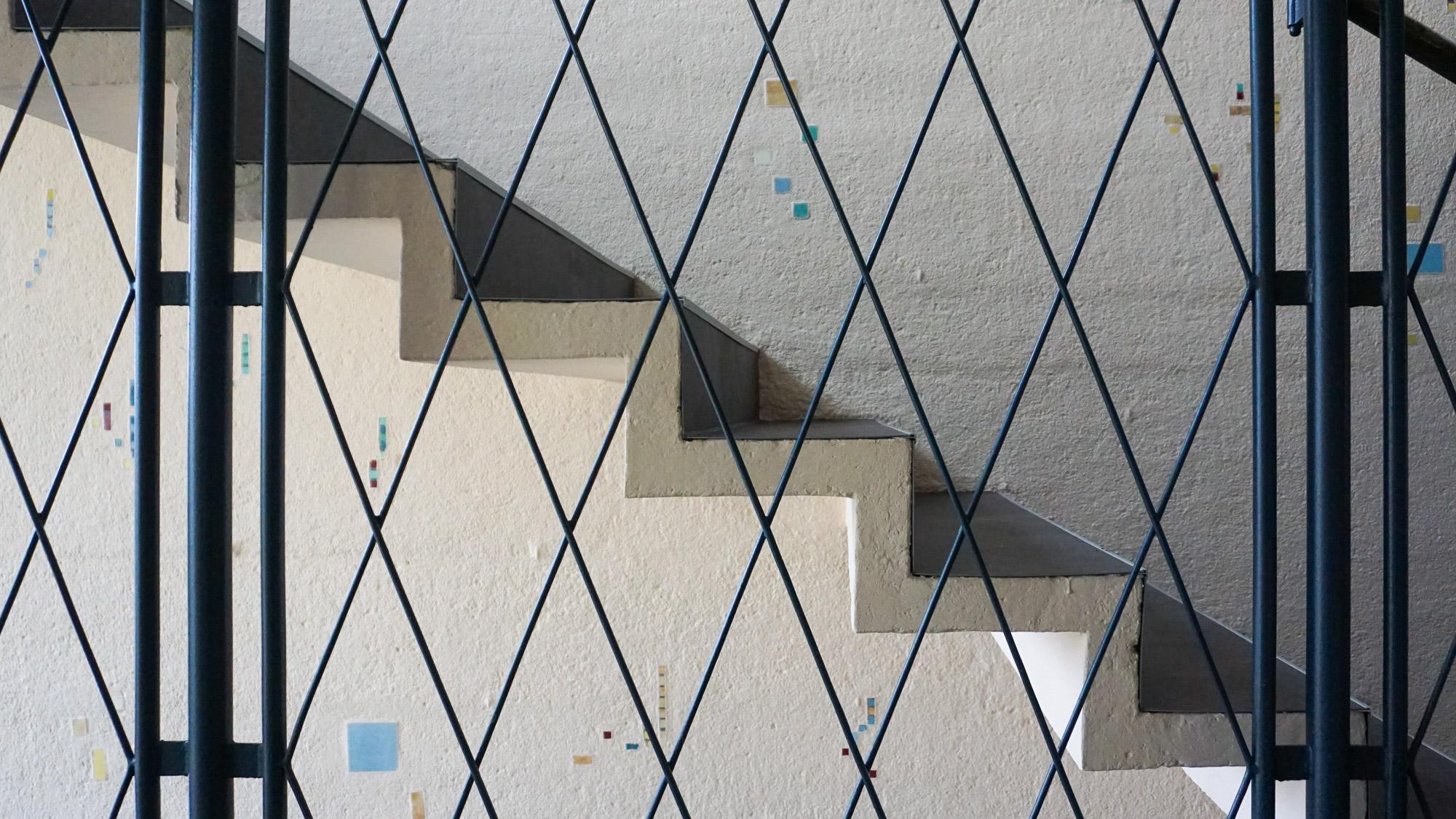 Detail einer filigranen Treppe mit Metallgeländer und kleinen Keramikverzierungen an der Wand