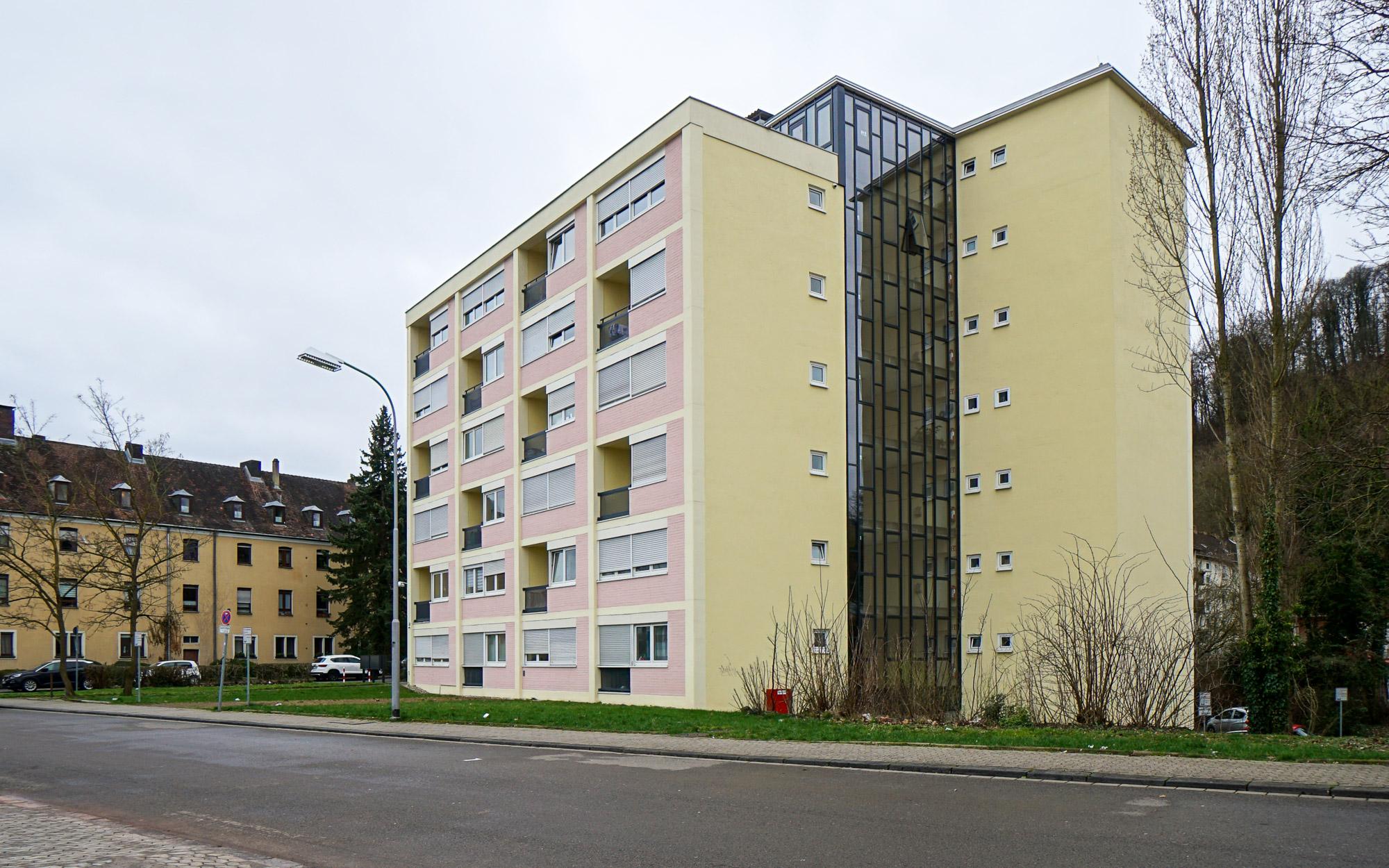 Gelb und rosa gestrichenes, sehr kompaktes Wohngebäude mit gläsernem Treppenhaus