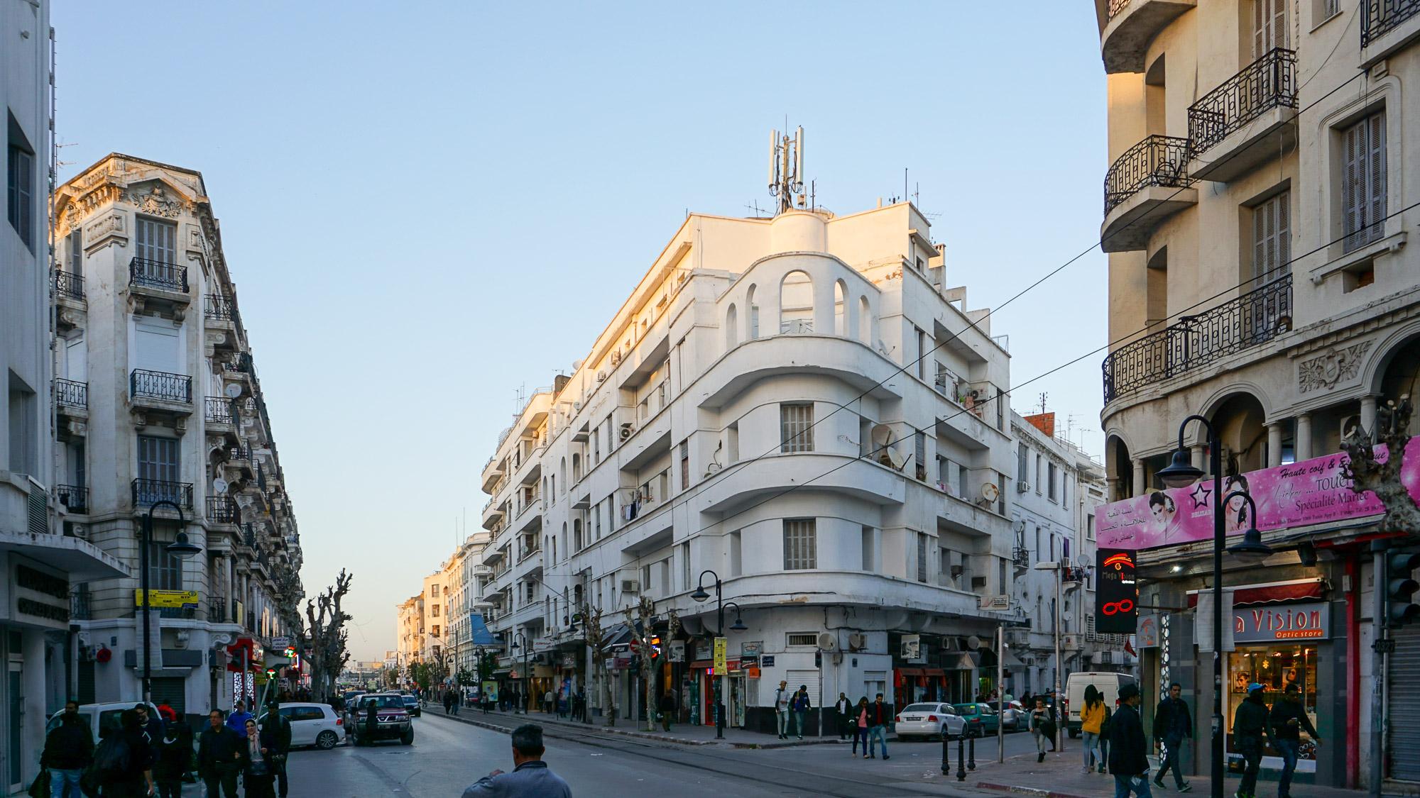 Straße mit weißen Wohn- und Geschäftshäusern im Abendlicht