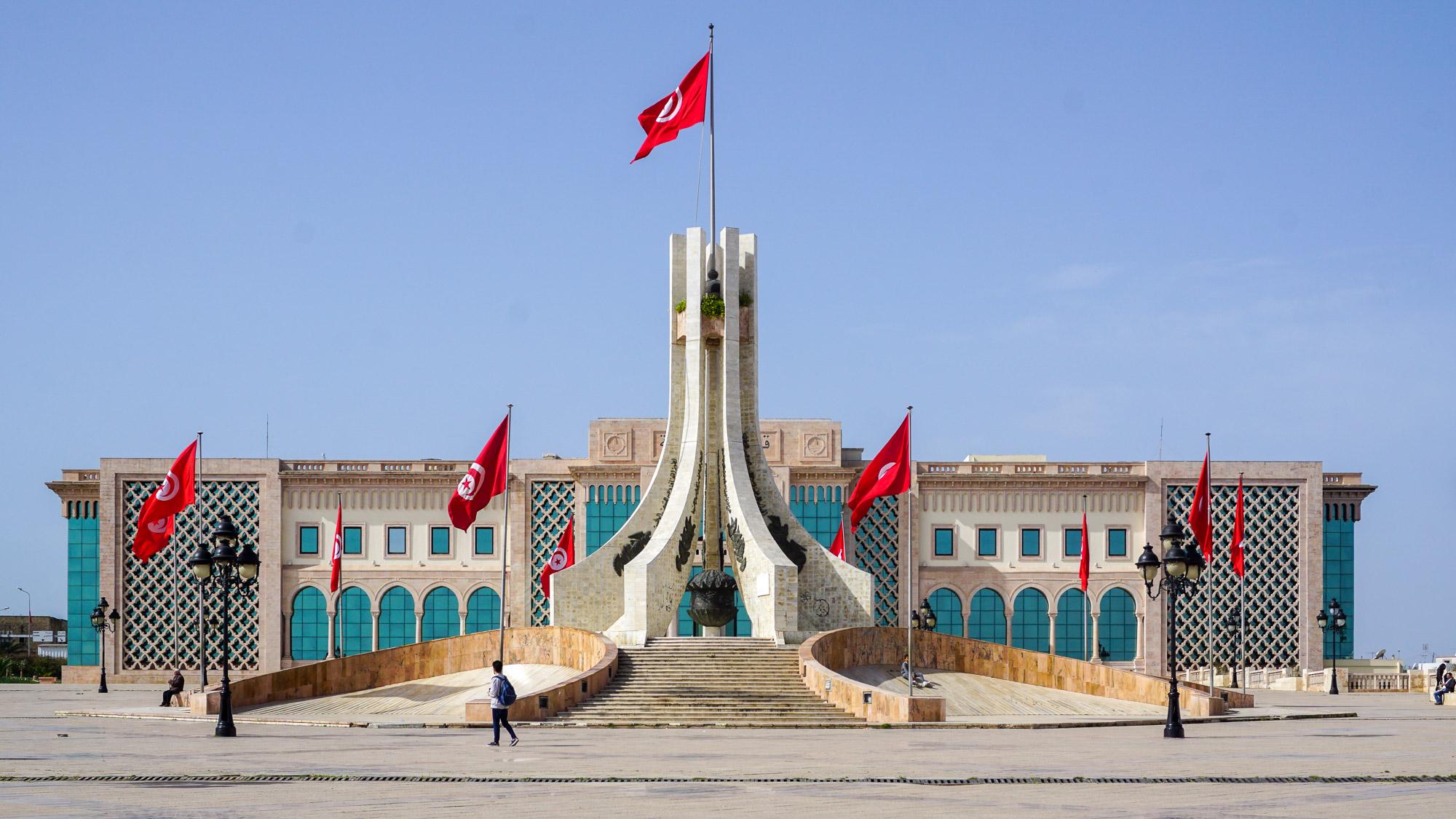 Fahnengeschmücktes Verwaltungsgebäude und Denkmal