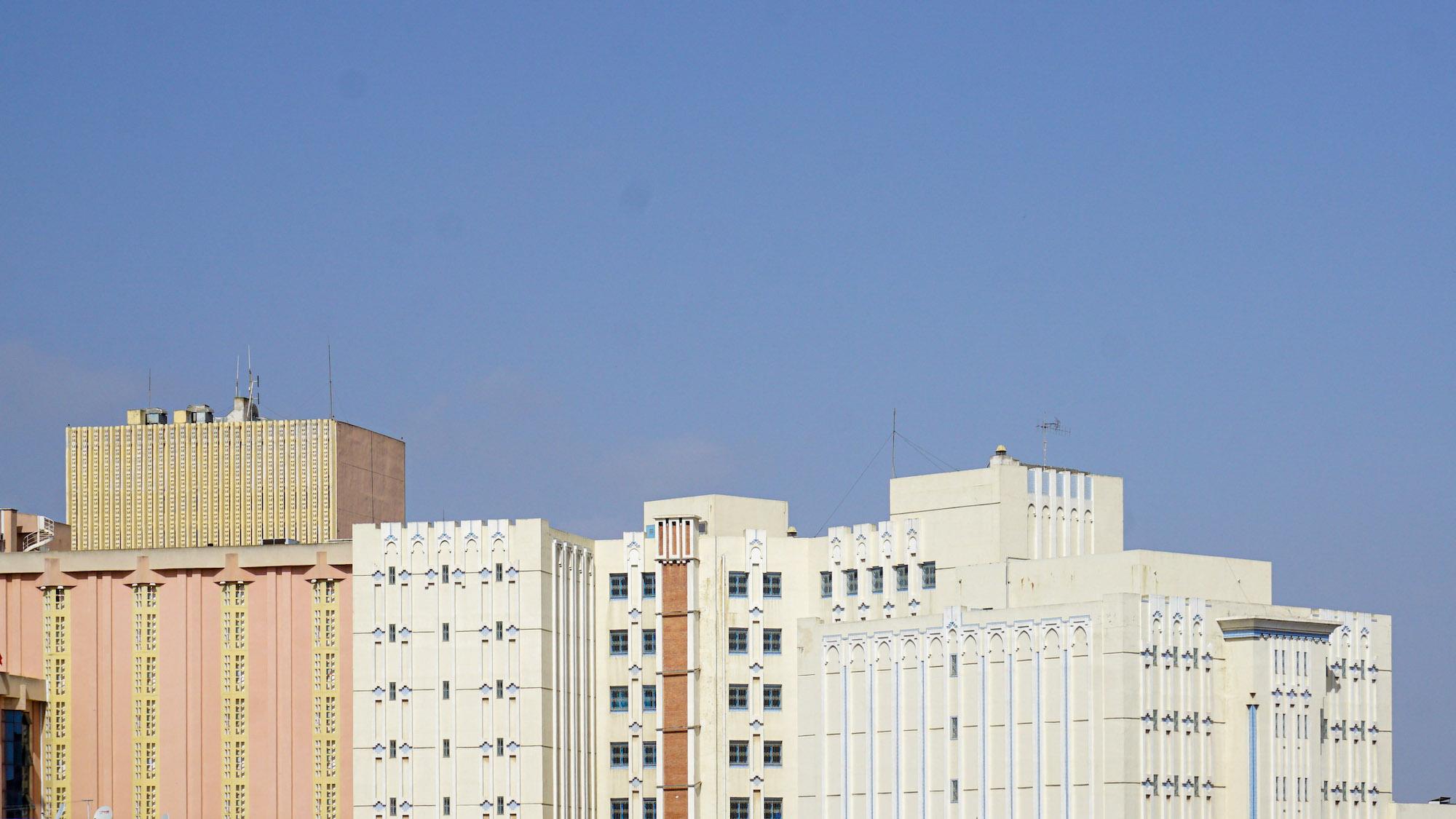 Verschiedene orientalisch wirkende Fassaden in Pastellfarben vor blauem Himmel