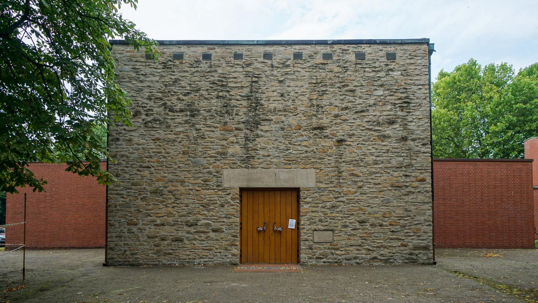 Blick auf eine Natursteinmauer mit Holztür.