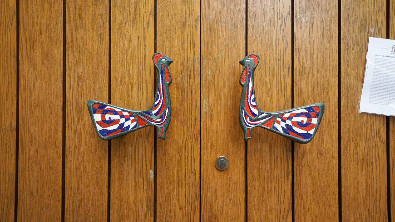 Hahnenförmige Handgriffe an der Eingangstür zur Heilig-Geist-Kirche in Essen-Karnap