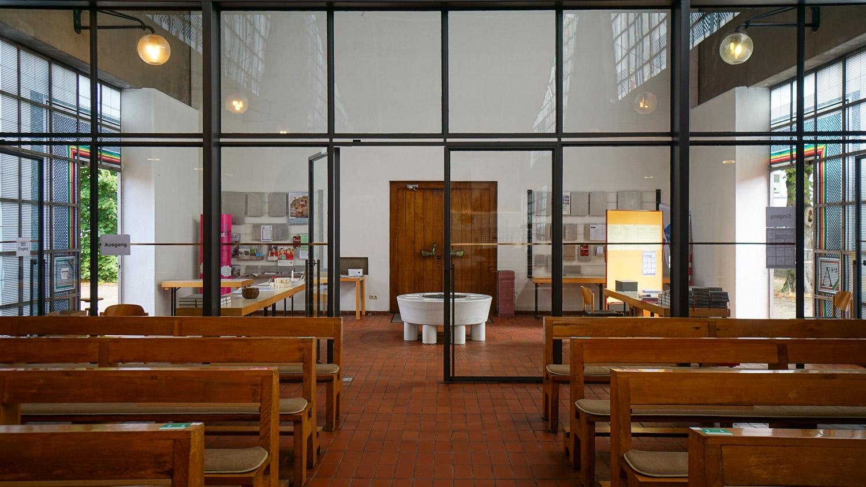 Blick vom Kirchenraum durch eine Glaswand auf den Eingangsbereich der Heilig-Geist-Kirche in Essen-Karnap