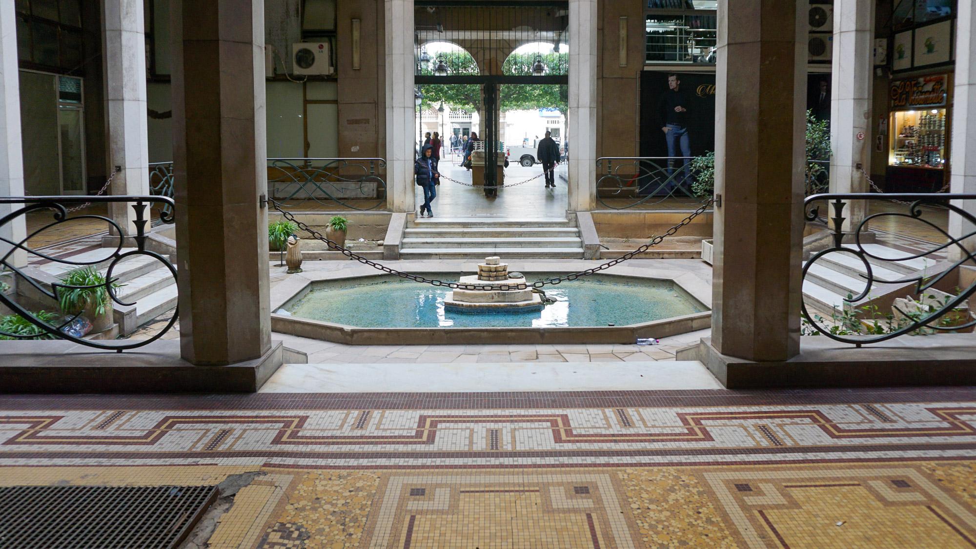 Innenhof eines älteren Gebäudes mit Springbrunnen und Mosaikfußboden