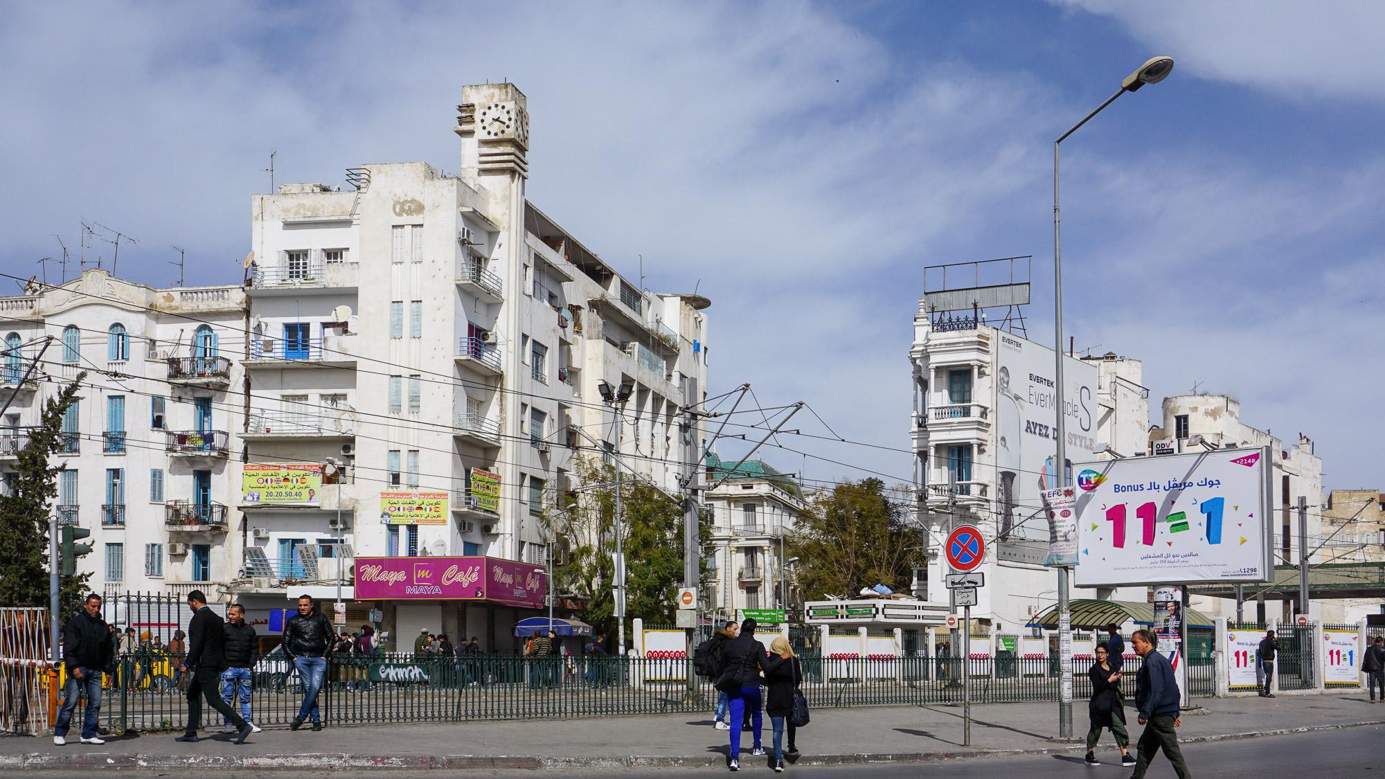 Wohngebäude mit kleinem aufgesetztem Uhrturm, im Vordergrund Menschen und Tramgleise