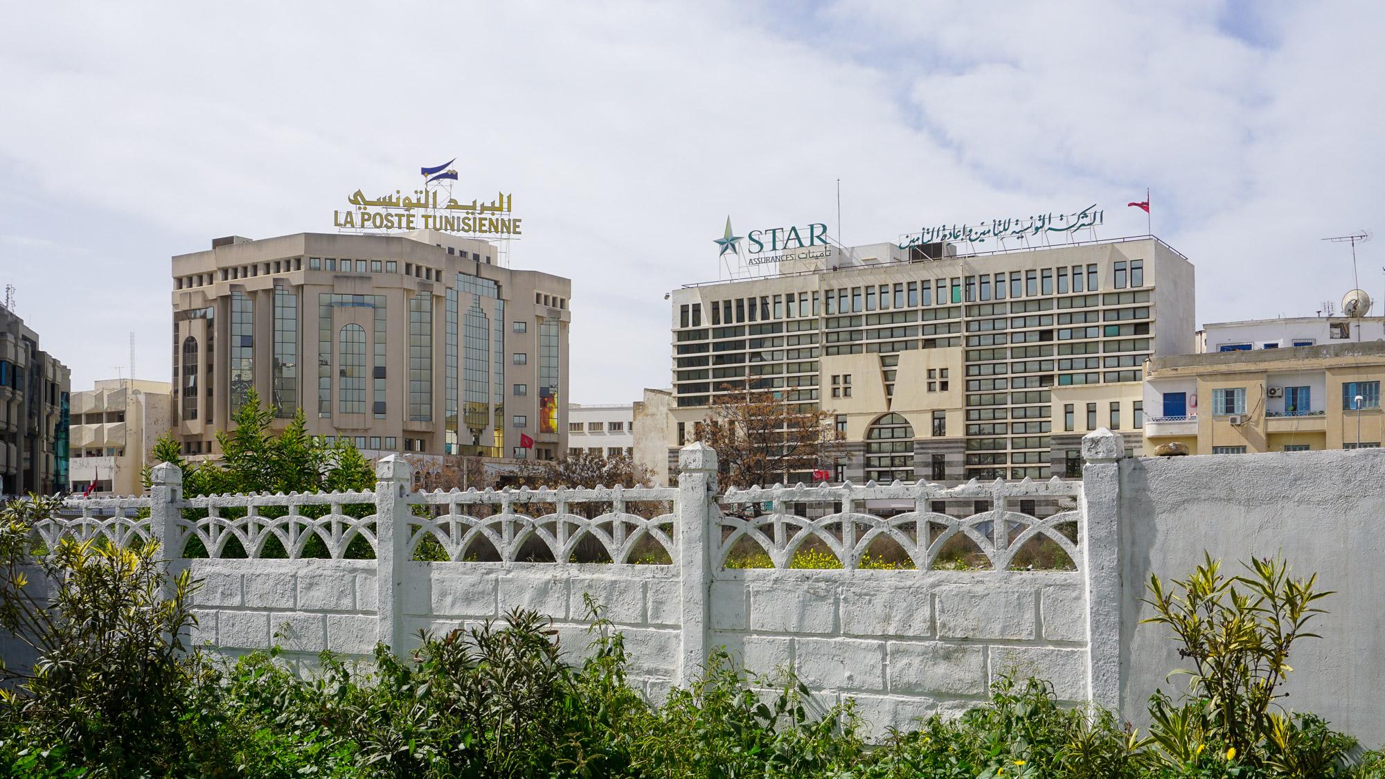Hauptpost und Verwaltungsgebäude, mit viel Glas und verpsielten Formen, davor ein weißer Zaun