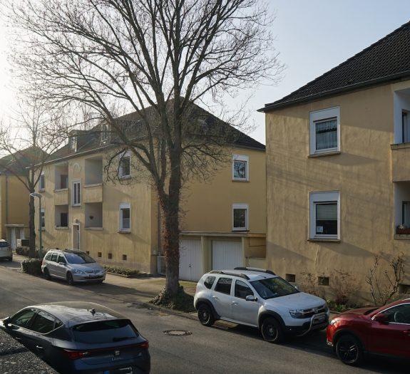 Wohnstraße mit gelber Häuserzeile und parkenden Autos