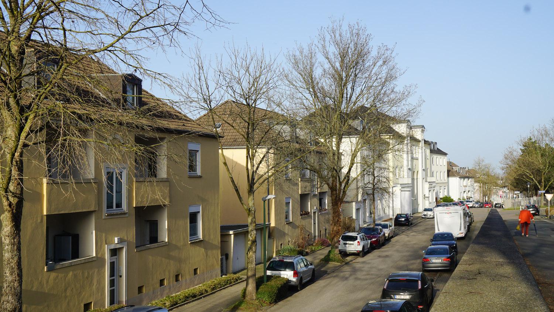 Leicht erhöhter Blick auf eine Wohnstraße, eine ältere Frau läuft ins Bild