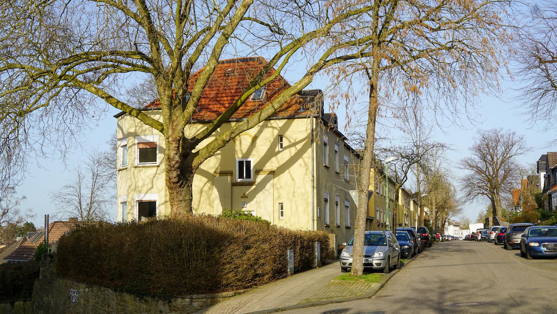 Ruhige Wohnstraße mit älteren zweistöckigen Wohnhäusern.