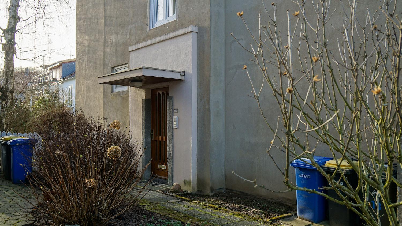 Eingang zu einem Mehrfamilienhaus, davor bunte Mülltonnen