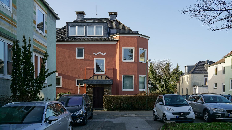 rot gestrichenes älteres Mehrfamilienhaus mit Fassadenverzierung