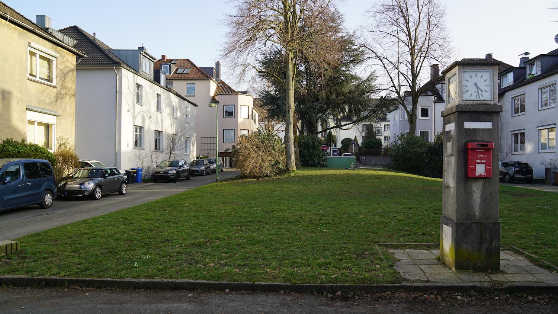 Grünanlage, umgeben von älternen Wohnhäusern. Im Vordergrund eine öffentliche Uhr auf einer Betonstele.