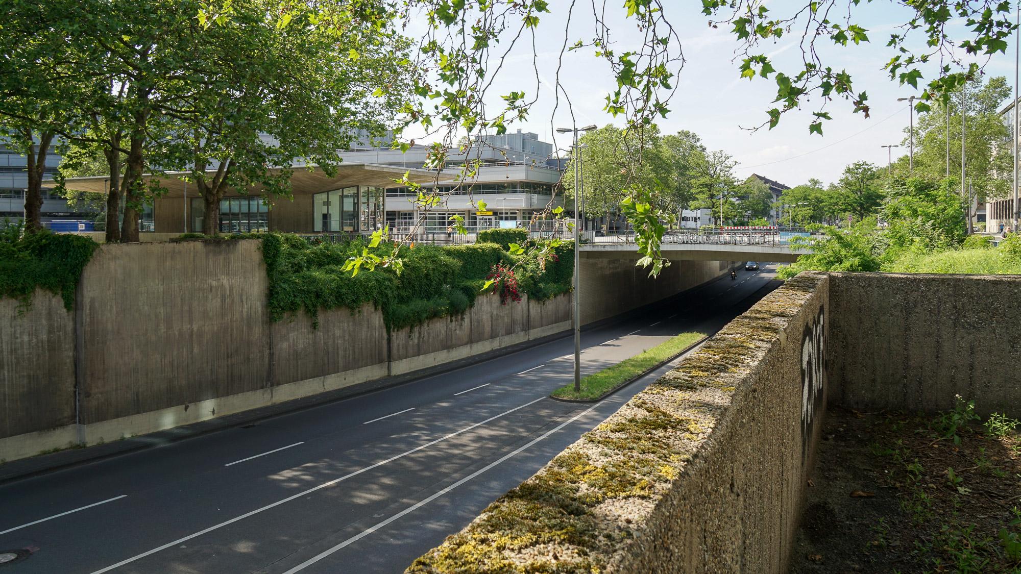 Vierspurige Straße wird unter einem Platz hindurchgeführt. Im Hintergrund sieht man Universitätsbauten.