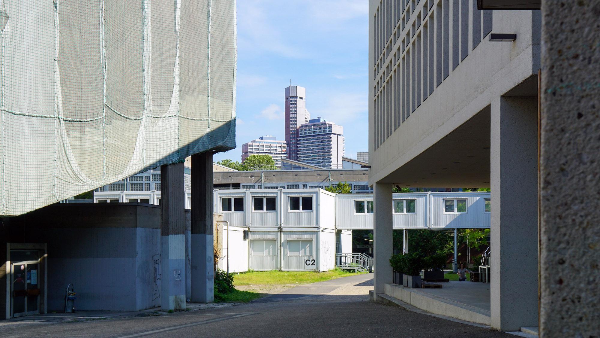 Unübersichtliche Stelle mit mehreren Gebäuden, Baucontainern und einem Hochhaus im Hintergrund