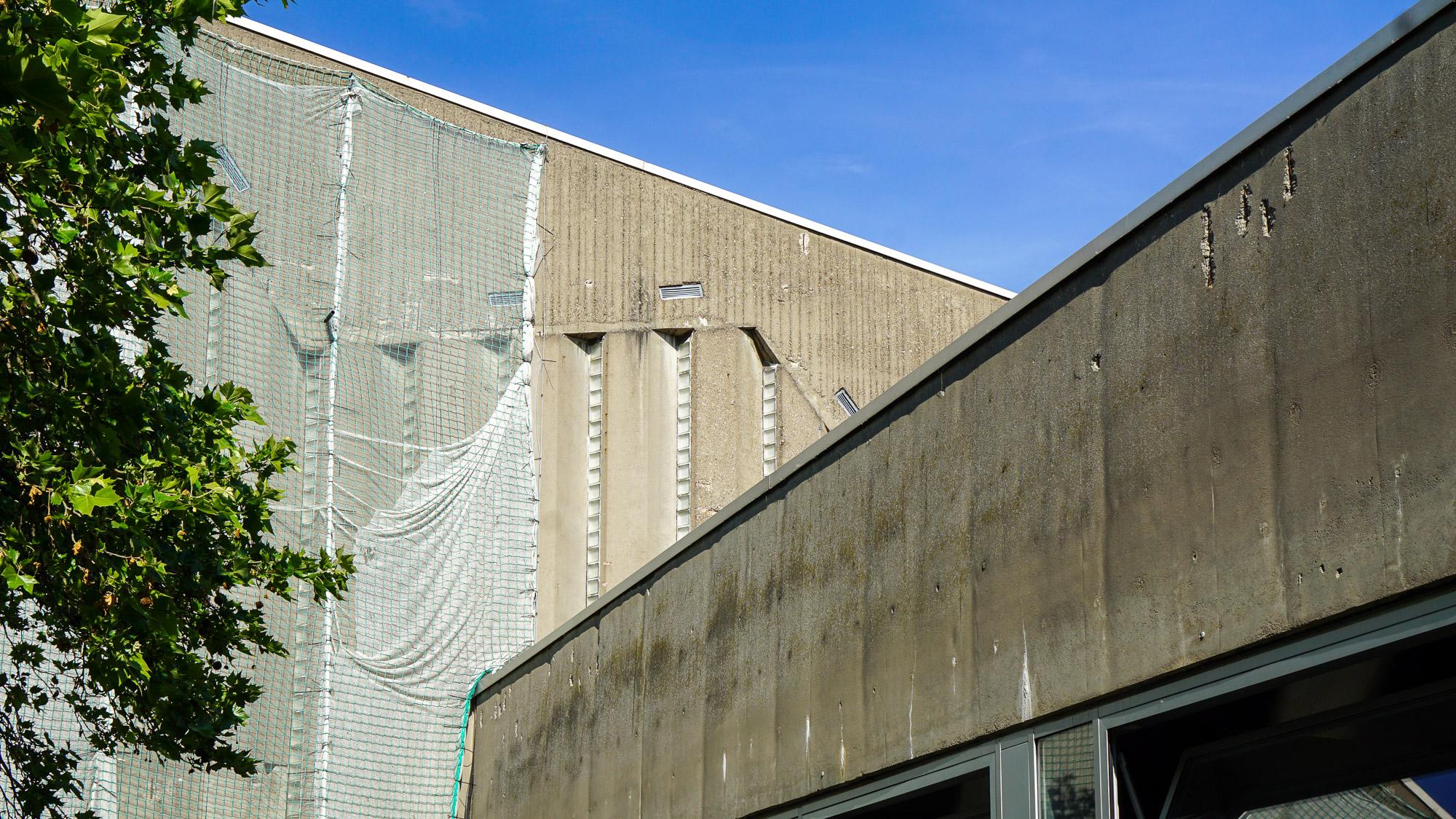 Betonfassade des Hörsaalgebäudes. Sie ist mit Netzen verkleidet, aber man kann noch etwas von der künstlerischen Gestaltung sehen.