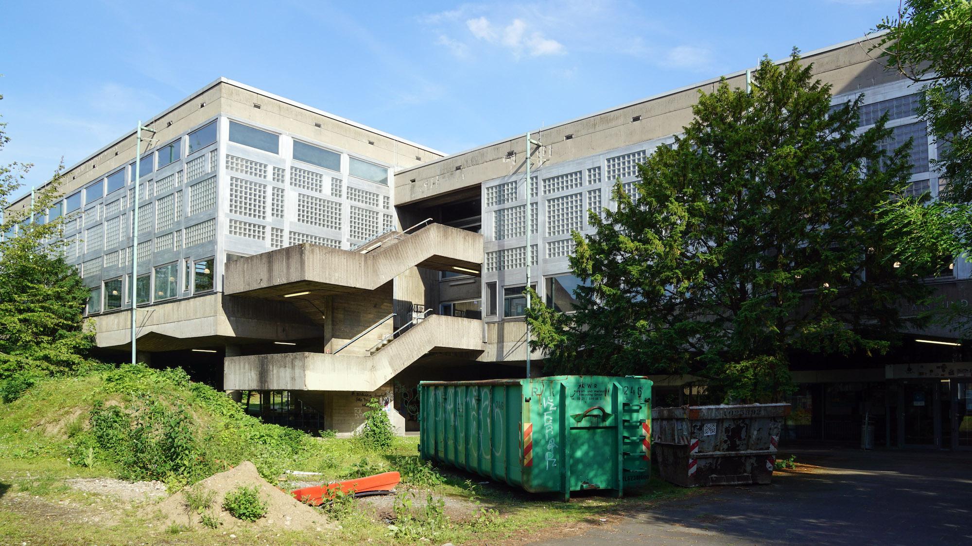 Bibliotheksgebäude aus Beton und großen Fensterfronten, im Vordergrund eine wuchtige Außentreppe, Baucontainer und andere Baumaterialien.