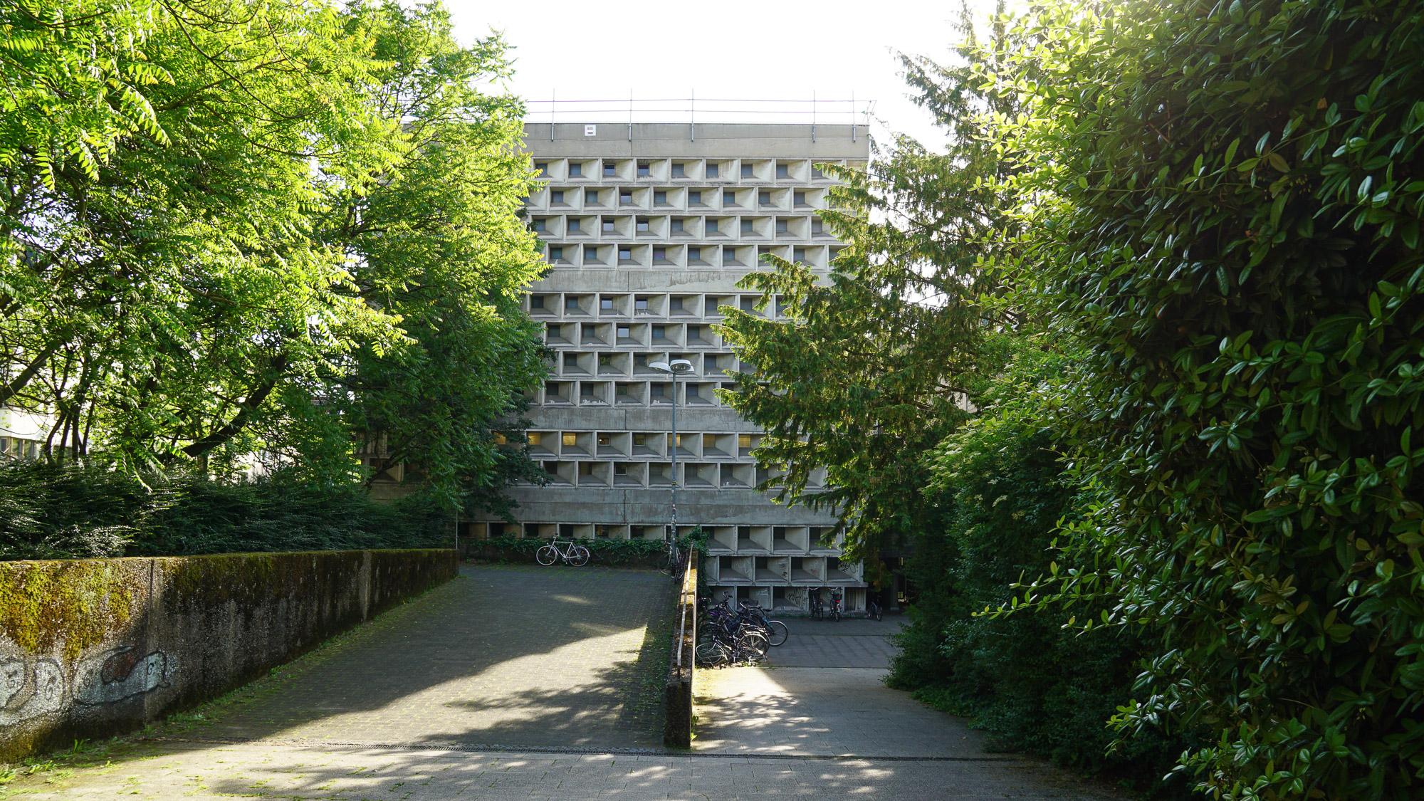 Betongebäude mit schießschartenähnlichen Fenstern. Es wirkt abweisend. Links und rechts Bäume und Sträucher, einige geparkte Fahrräder