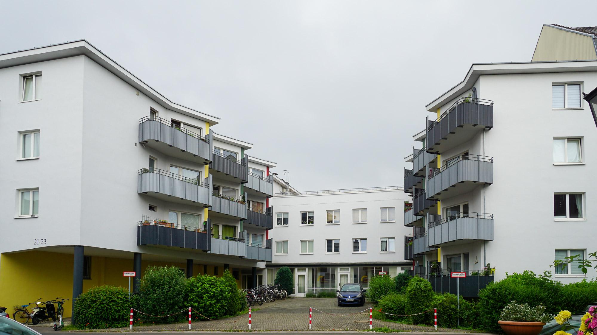 Vierstöckig, locker aufgebautes Wohnhaus mit abgerundeten Balkonen