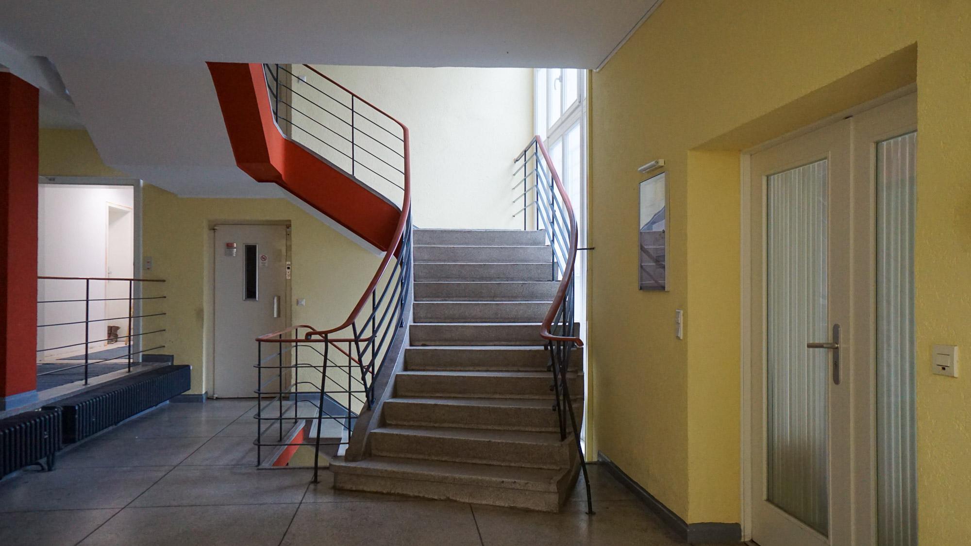 Treppenhaus eines Wohnhauses mit gelben Wänden sowie rot abgesetztem Geländer