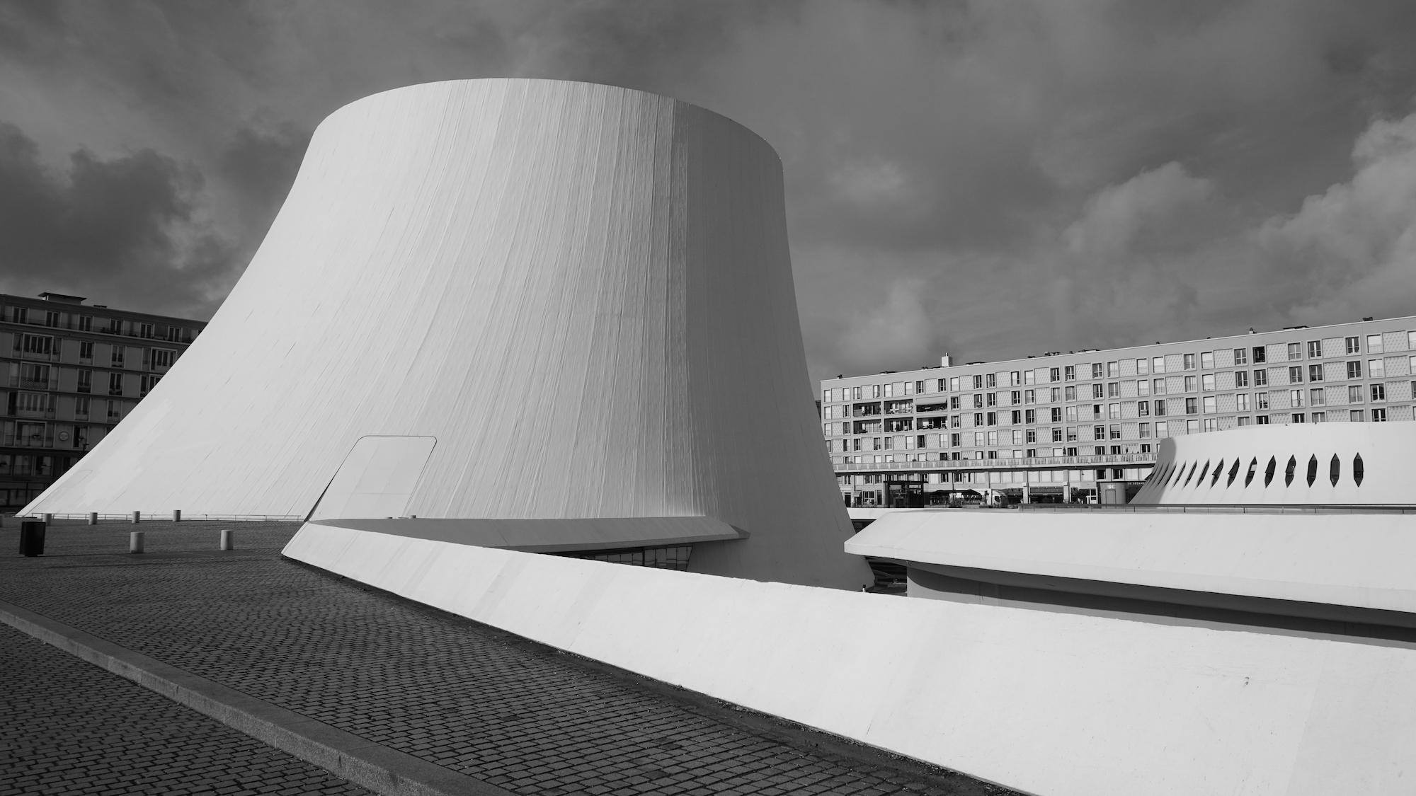 vulkanförmiges weißes Bauwerk vor Wohngebäuden aus der Nachkriegszeit