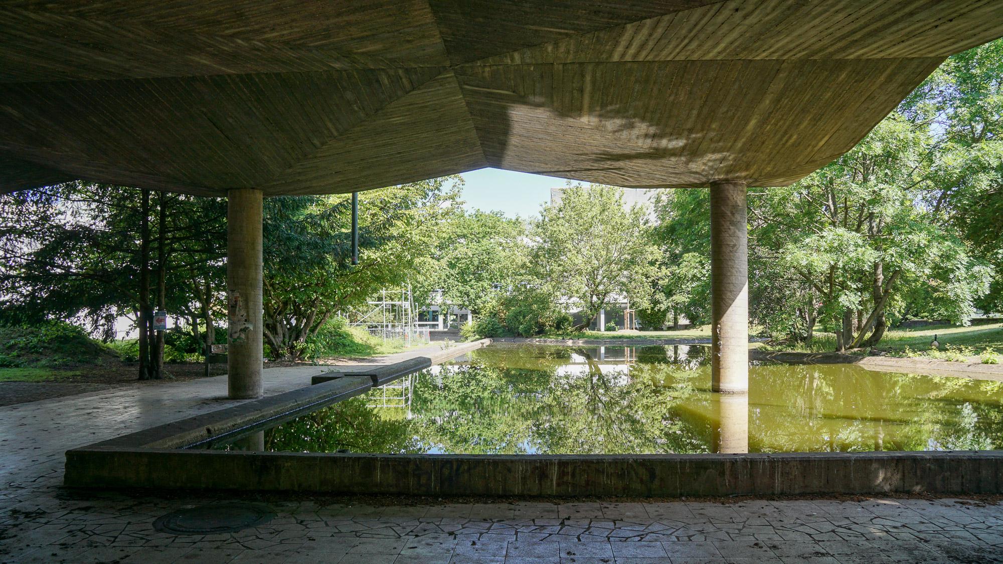Ein Wasserbecken und Bäume. Zwei Säulen tragen ein Betondach, das bis über das Wasserbecken reicht.