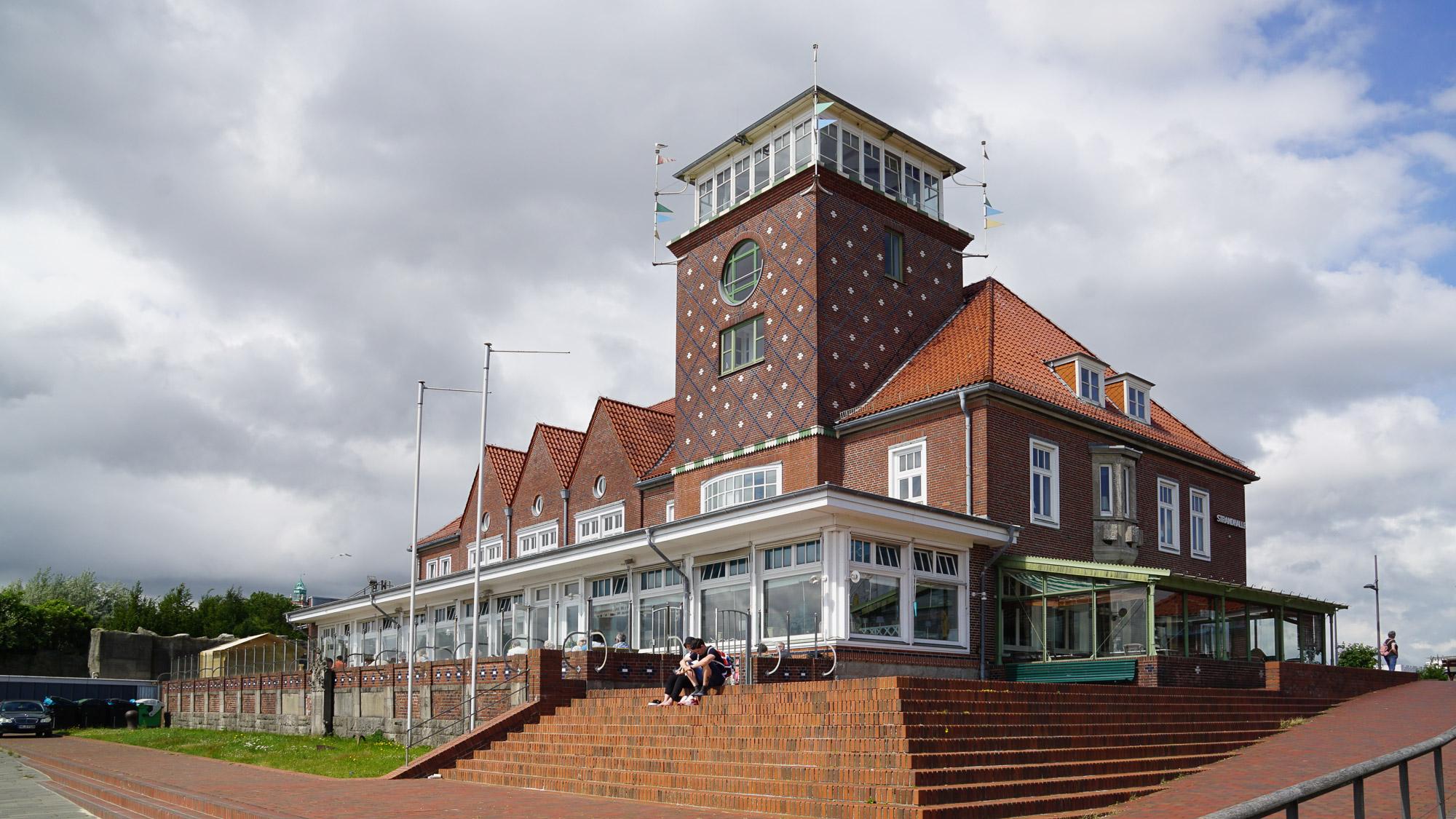 Ansicht eines Backsteinhauses mit gemusterter Fassade, im Erdgeschoss Gastronomie