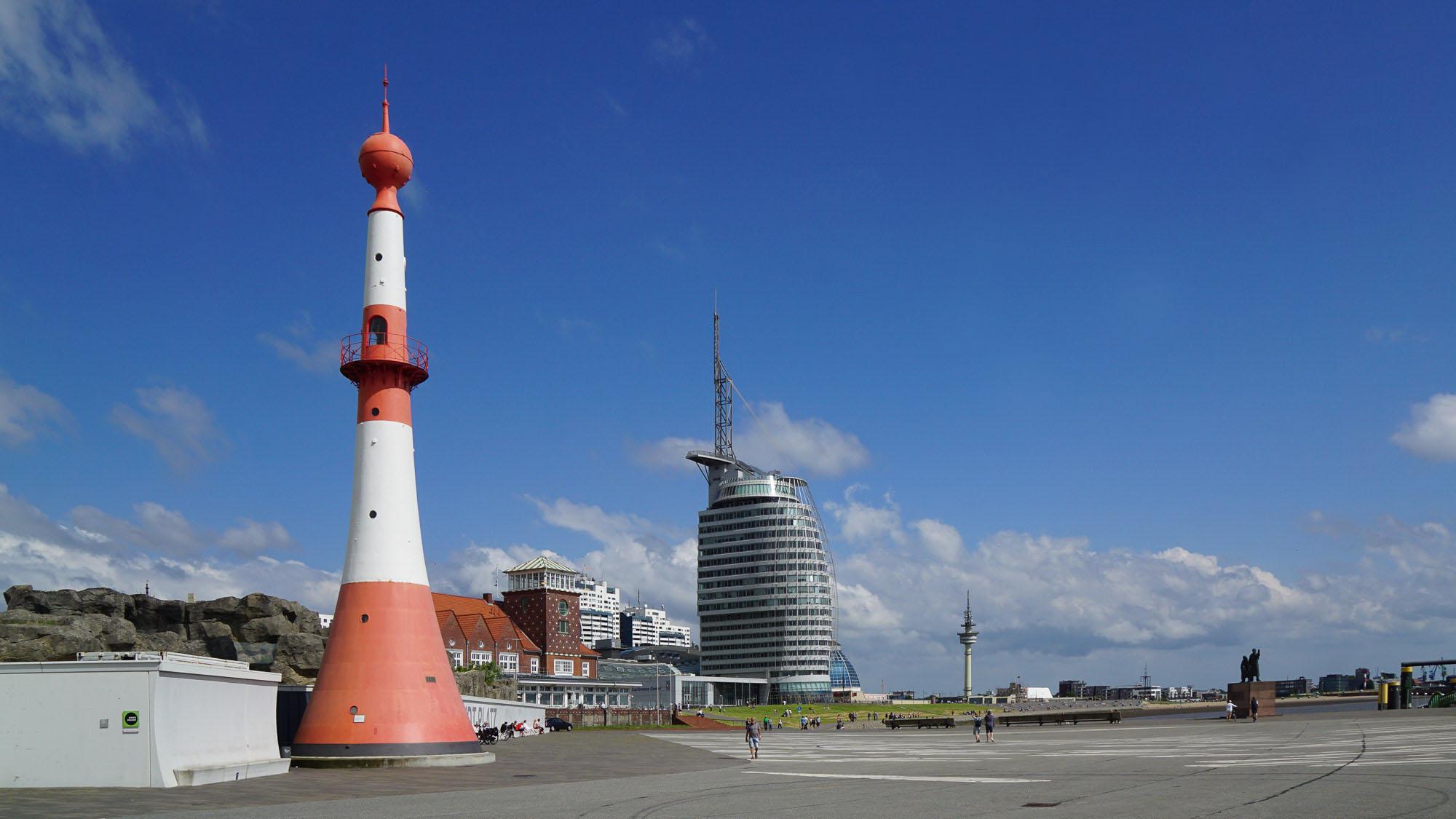 schlanker rot-weißer Leuchtturm im Vordergrund, modernes Gebäude im Hintergrund