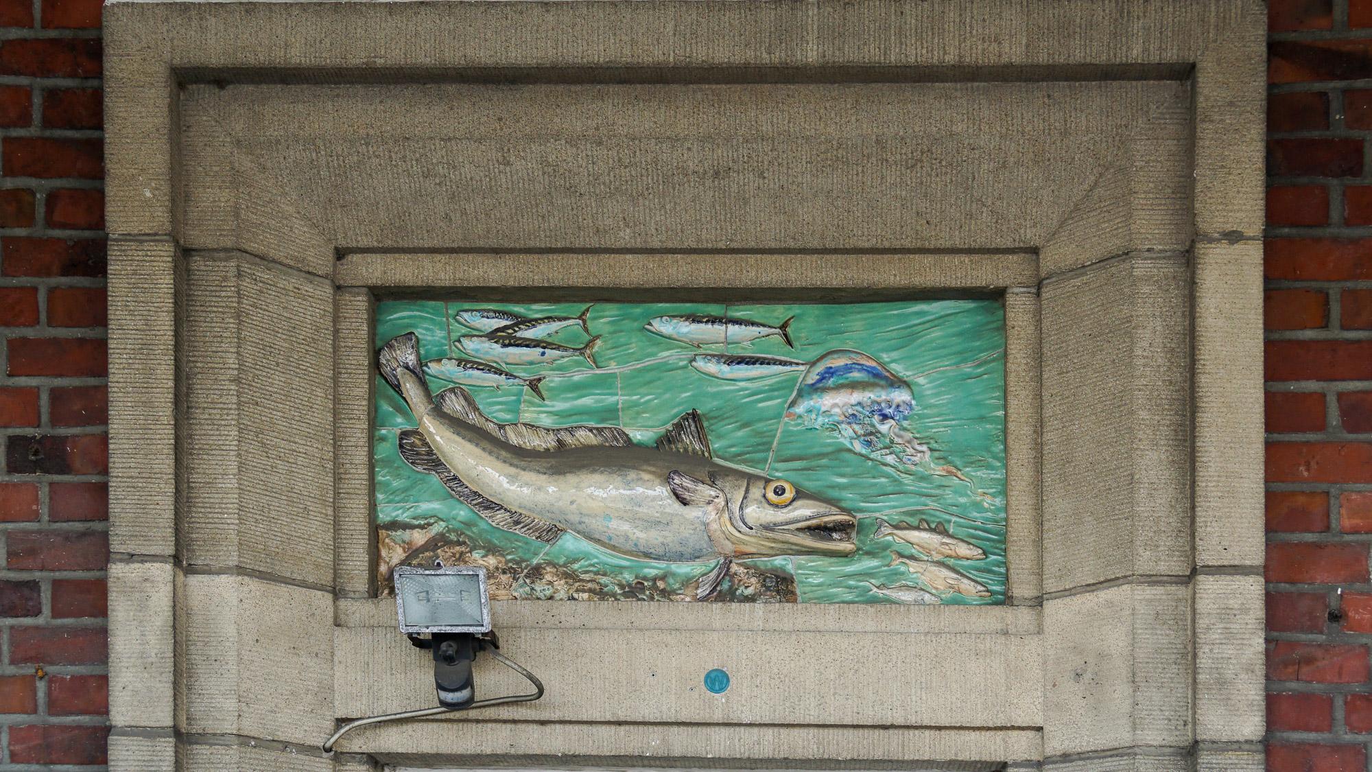 Gestaltungselement aus Keramik, das einen Fisch und eine Qualle zeigt. Umfasst von Stein als Türsturz.