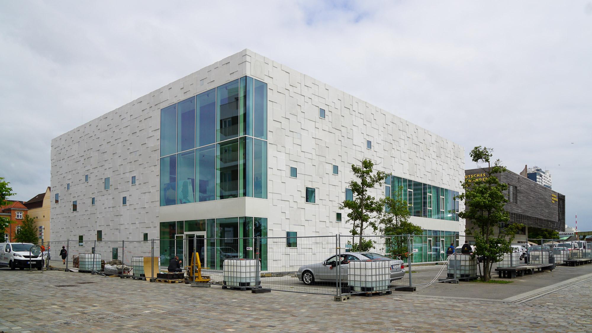Dreistöckiges kompaktes Gebäude mit heller, aufgelockerter Fassade und grün getönten Fenstern