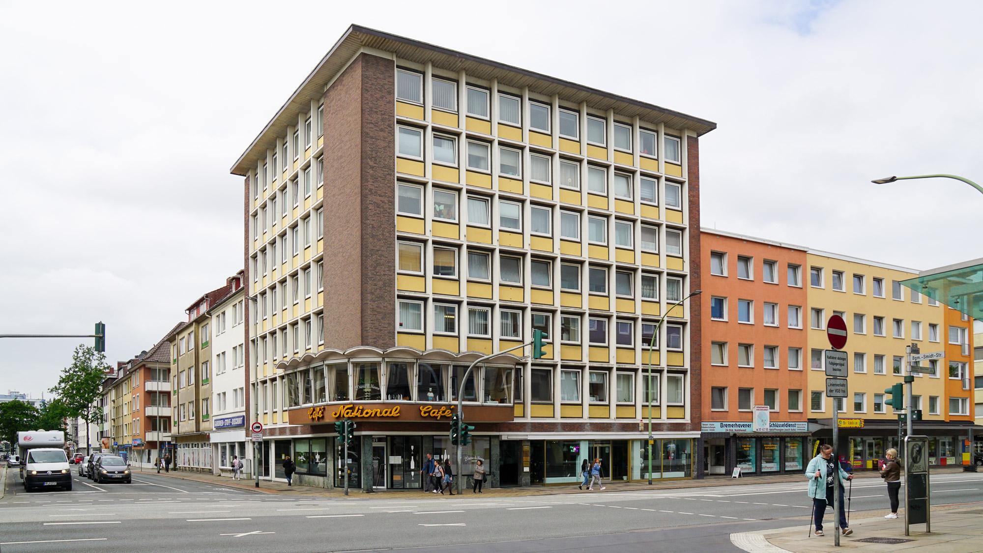 """siebenstöckiges Eckhaus mit gelb-weißer Fassade. Erker mit Beschriftung """"Café National"""""""