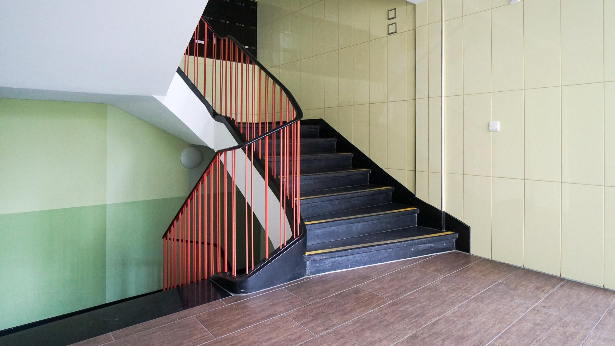 Treppenhaus mit gelben Wandkacheln und rotem Treppengeländer