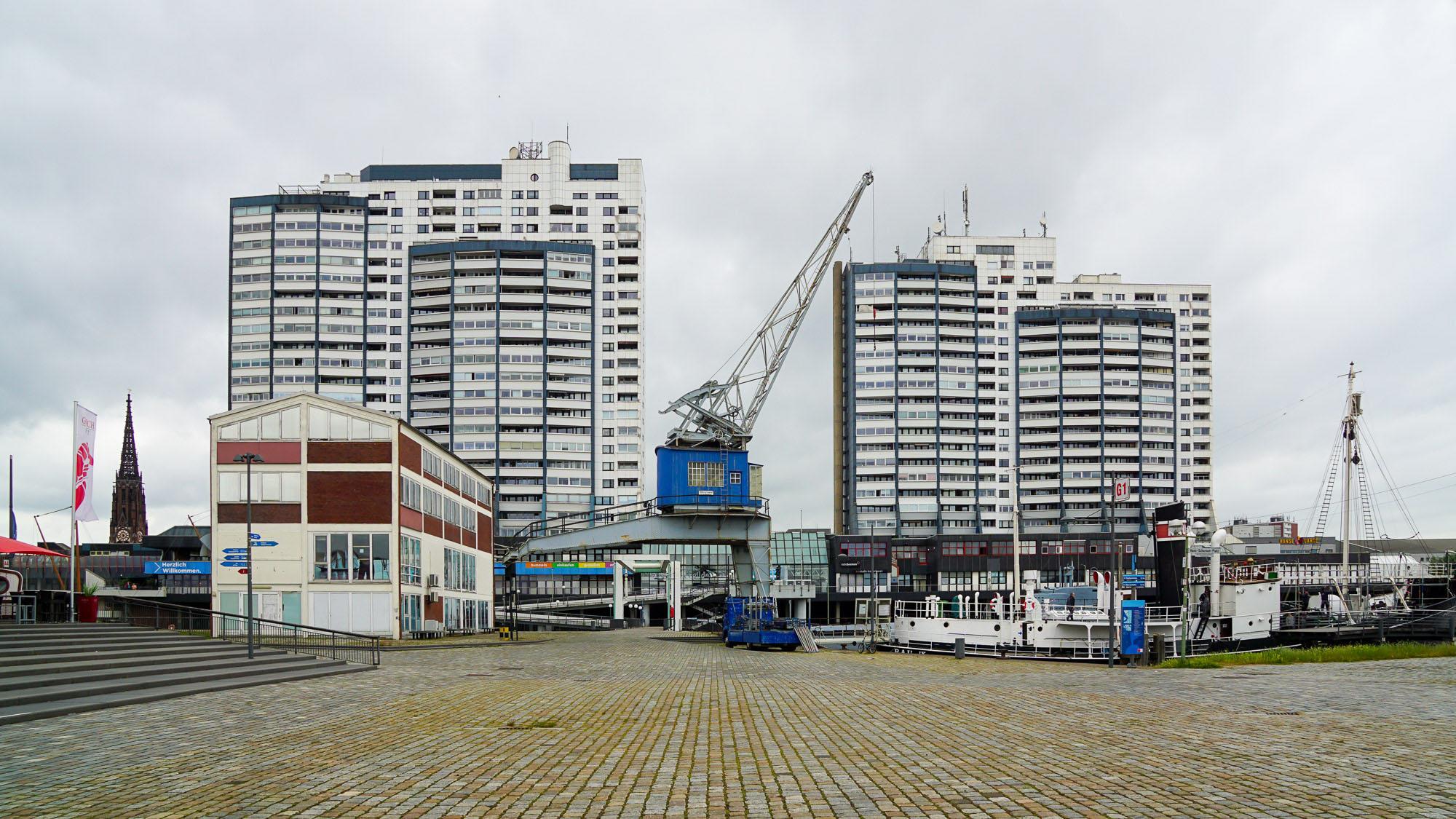 Hafenambiente. Wohnhochhäuser mit blauweißer Fassade im Hintergrund, ein blauer Lastkran im Vordergrund