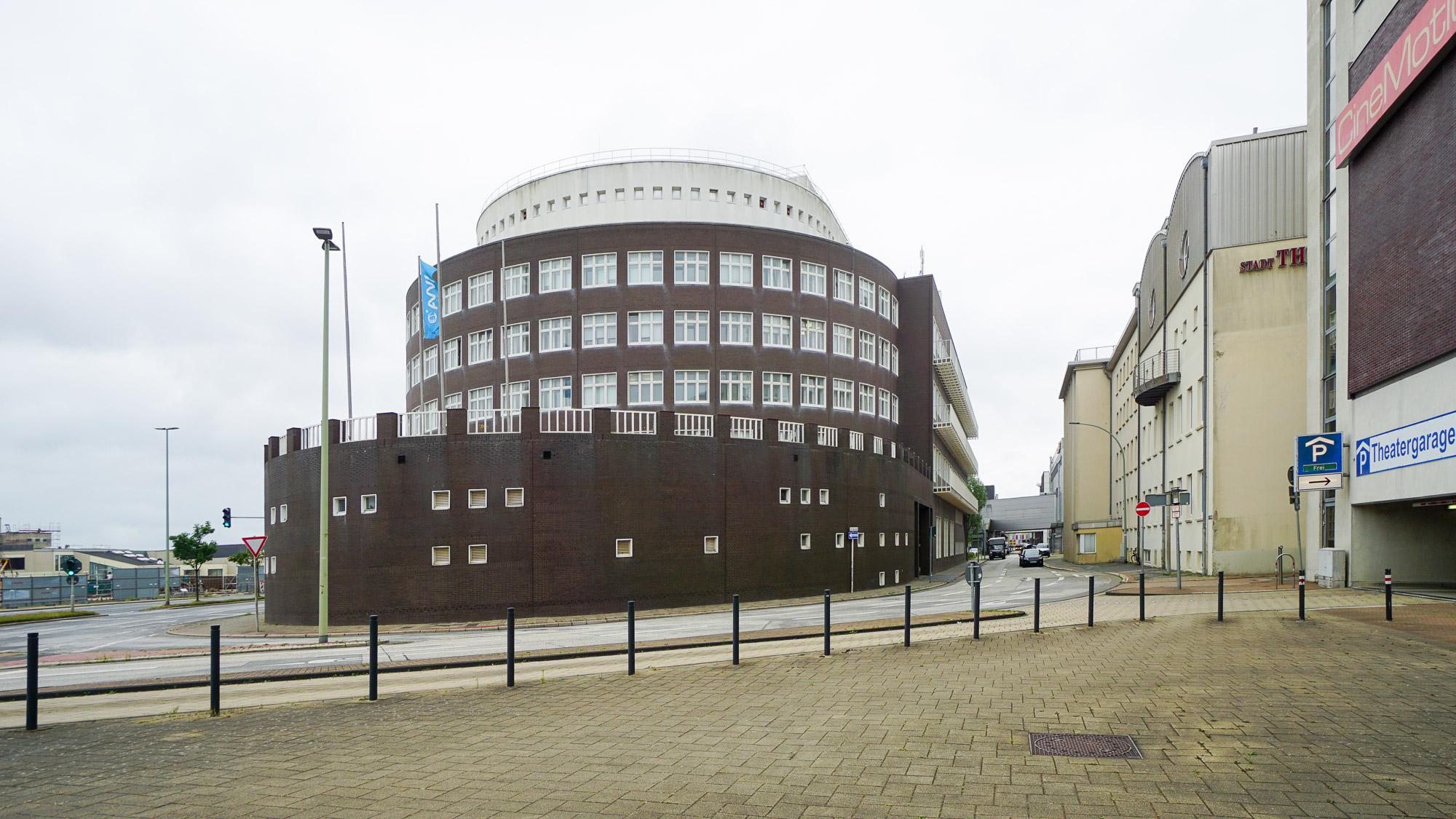 Halbrund geformtes mächtiges Gebäude in dunklem Backstein und oben weißem Material. Viele Fenster, Schiffsanmutung