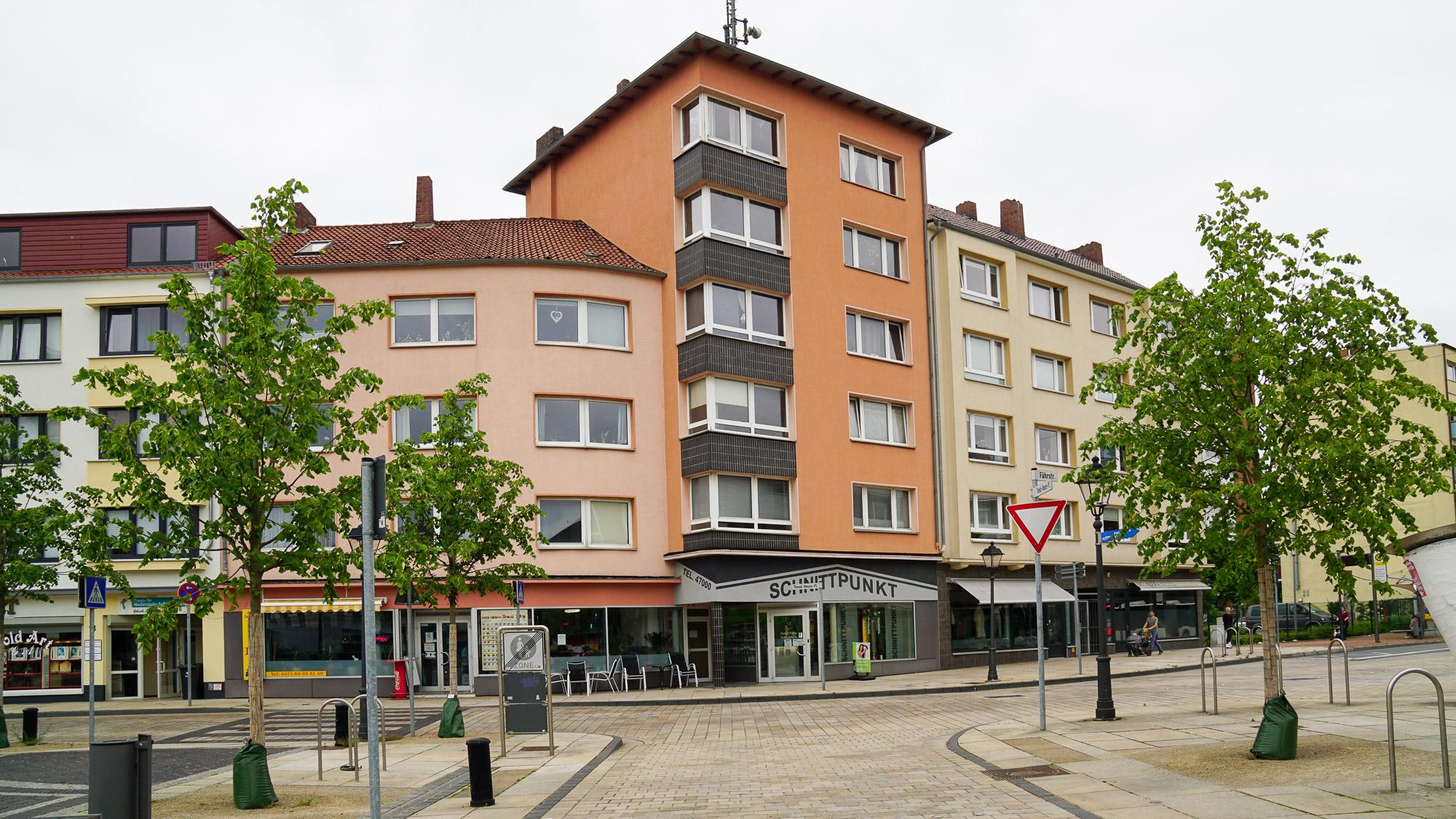 Wohnhäuser mit Geschäften im Erdgeschoss in kräftigen Ockertönen