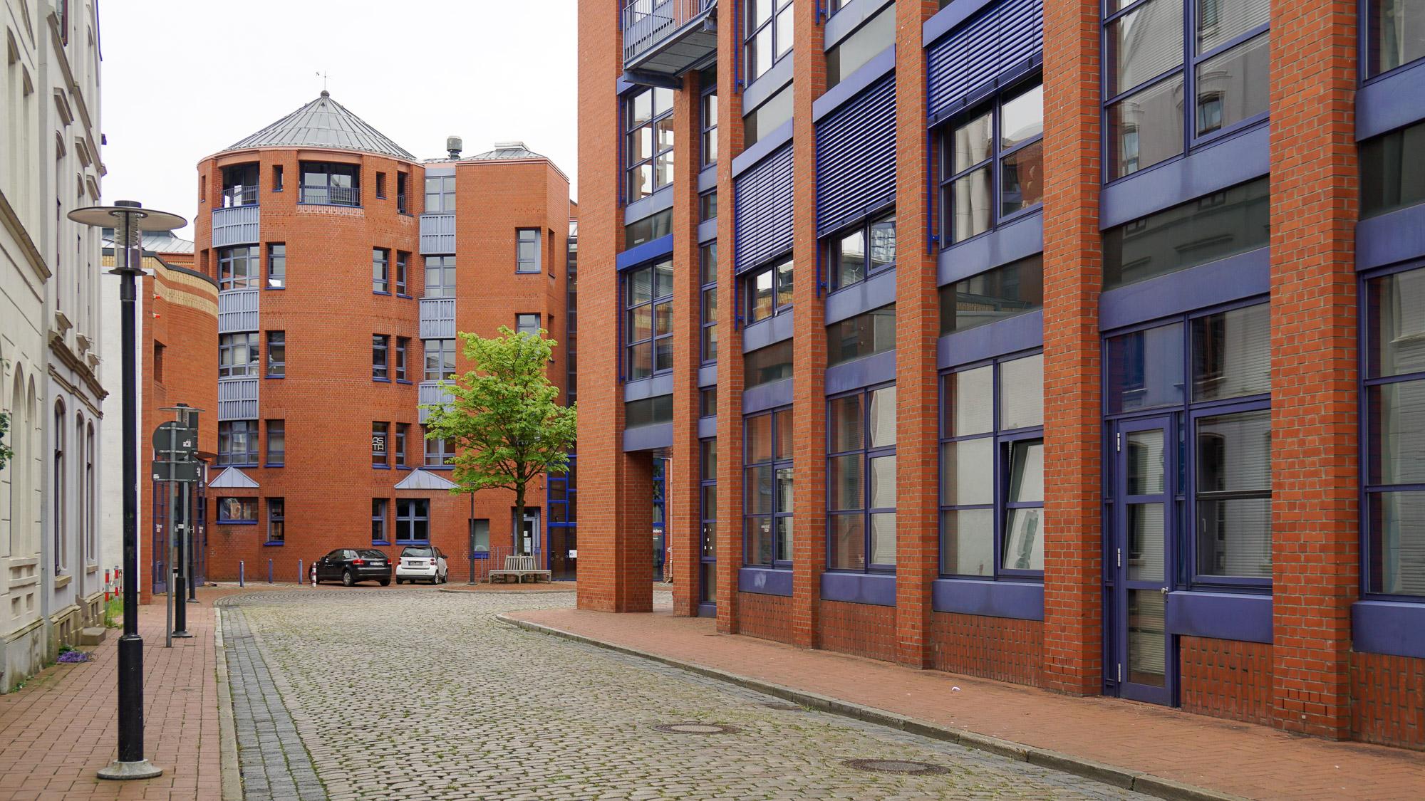 Gebäudeensemble aus rotem Backstein und blauen Metallstreben, Fensterrahmen etc.