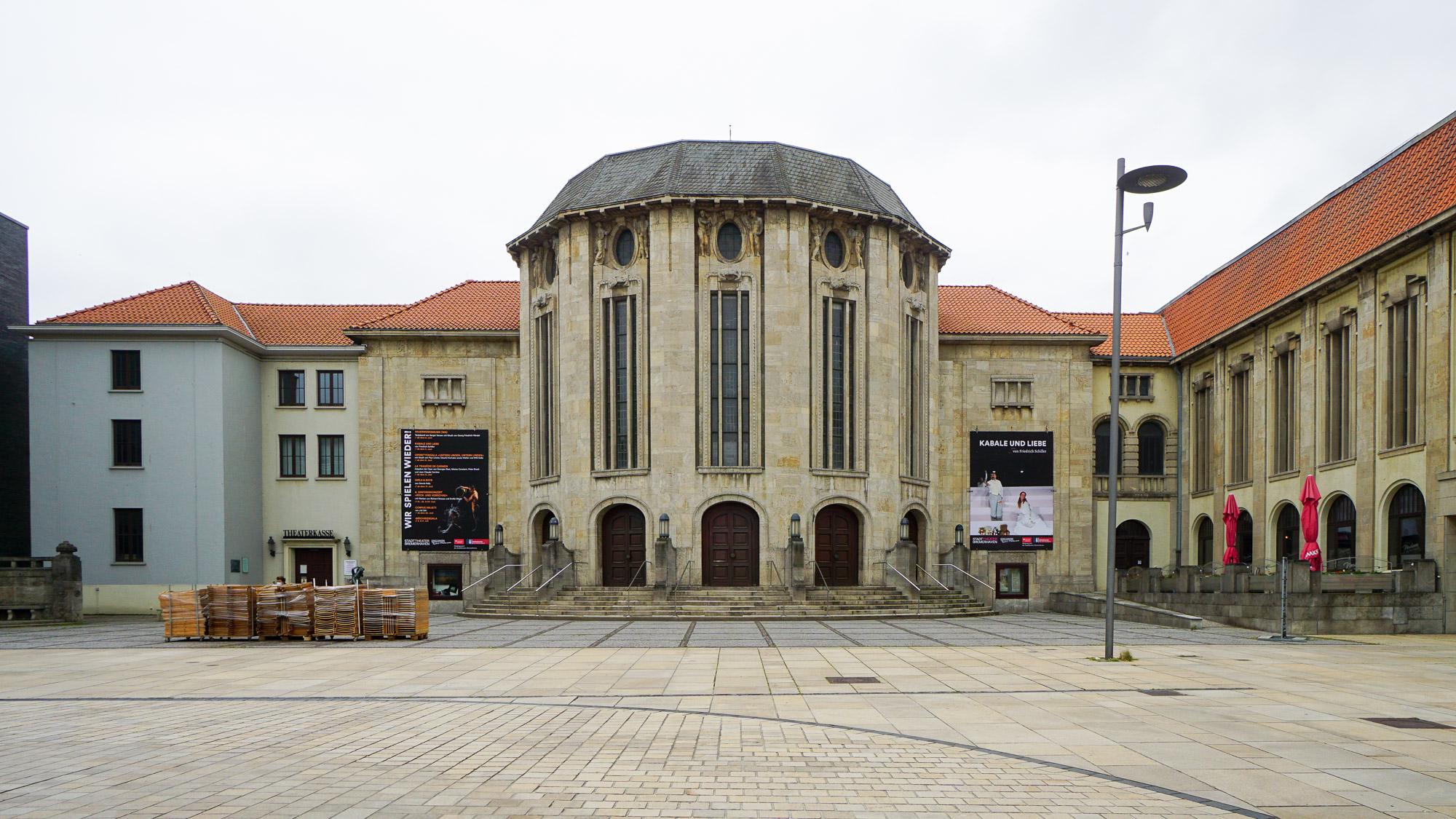 Theatergebäude aus Naturstein mit Veranstaltungsplakaten an der Fassade