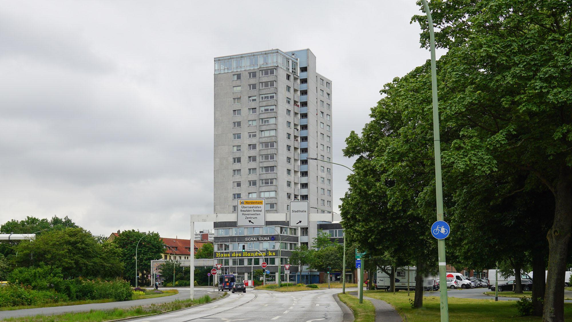 """Massiges Betonhochhaus, im unteren Teil gelb beschriftet mit """"Haus des Handwerks"""""""