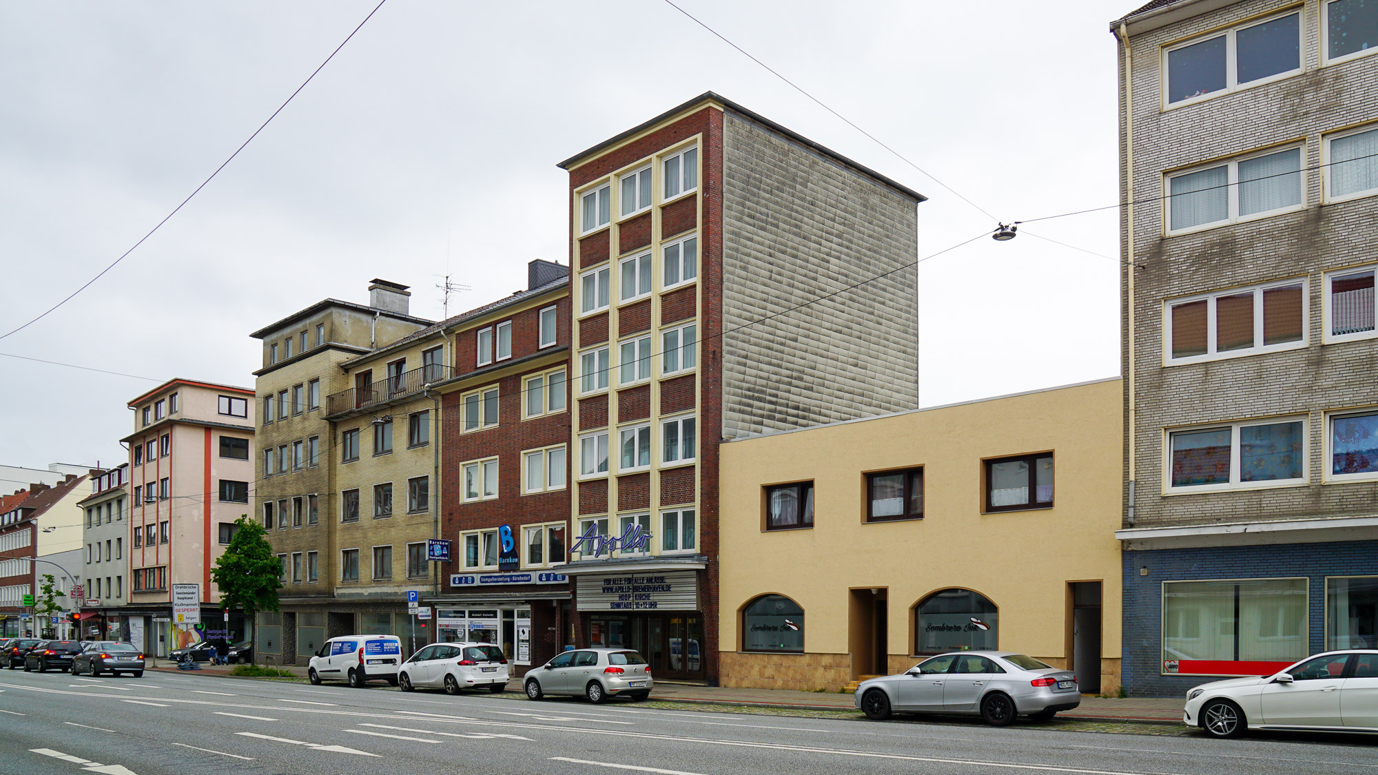 breite Straße mit gemischter Bebauung aus der Nachkriegszeit.