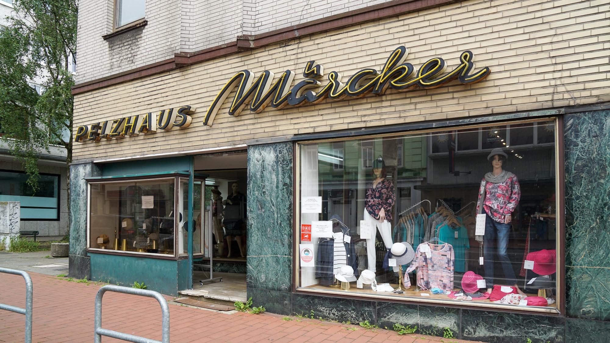 """Altmodisches Geschäft mit grüner Marrmorverkleidung und gelb geklinkerter Hausfassade. In alter Neonschrift: """"Pelzhaus Märcker"""""""