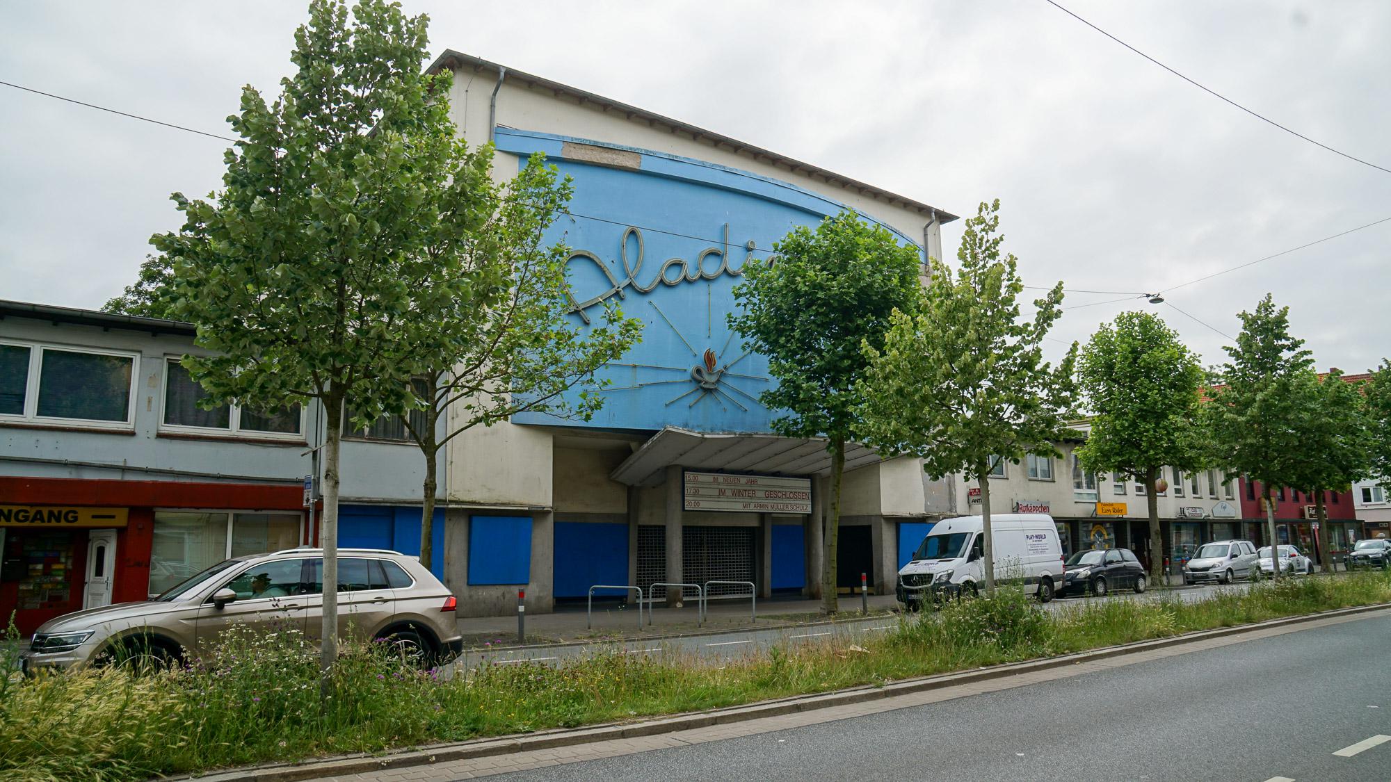 """Altes Kinogebäude mit gewölbter Fassade. In Neon der von einem Baum verdeckte Schriftzug """"Aladin"""""""